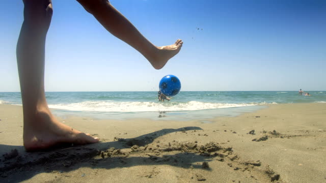 boy playing football. beach holiday - careless stock videos & royalty-free footage