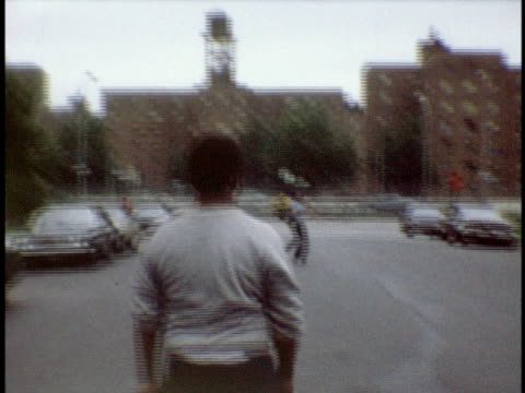 1973 MS Boy playing football on street / Bronx, New York