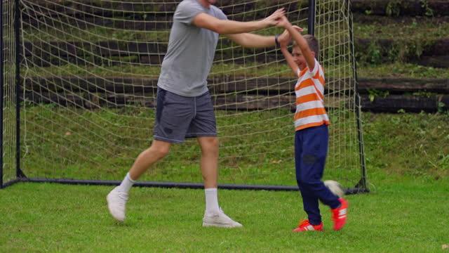 vídeos y material grabado en eventos de stock de chico jugando al fútbol con su padre y un amigo - padre soltero