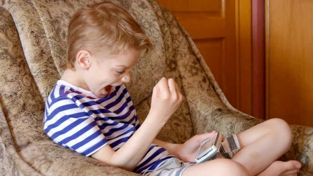 stockvideo's en b-roll-footage met jongen spelen op smartphone - alleen jongens