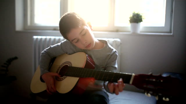 boy playing guitar at home - guitar stock videos & royalty-free footage