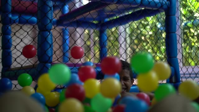 boy playing in plastic pool full colourful balls - sphere stock videos & royalty-free footage