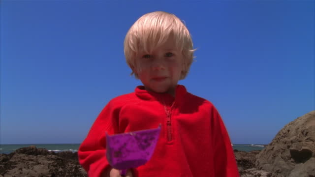 MS boy playing in sand with bucket and shovel near tide pool/ boy looking at camera and holding shovel aloft/ California