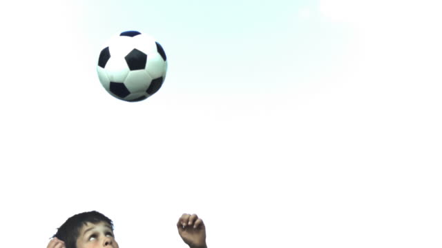 Boy playing in slow motion with a soccer ball
