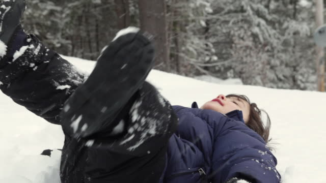 CU Boy (4-5) playing in snow outdoors, falling down on ground and licking snow / Franconia, New Hampshire, USA