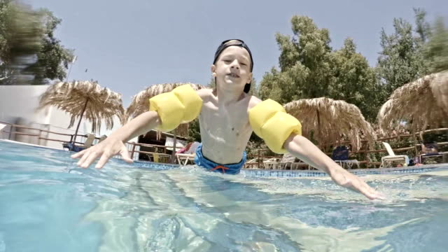 boy playing in swimming pool - arm band stock videos & royalty-free footage