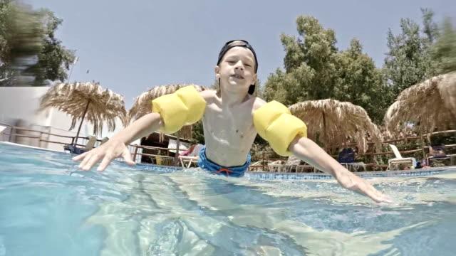 jungen spielen im pool - schwimmflügel stock-videos und b-roll-filmmaterial