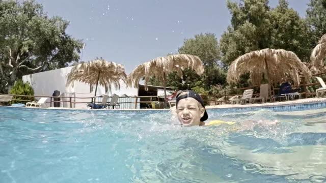 vídeos de stock, filmes e b-roll de garoto brincando na piscina - touca de natação
