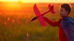 Boy playing in the field with a plane in his hands at sunset