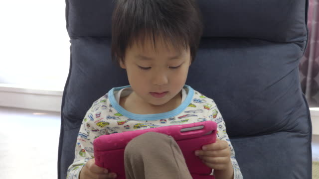 Boy playing in the tablet