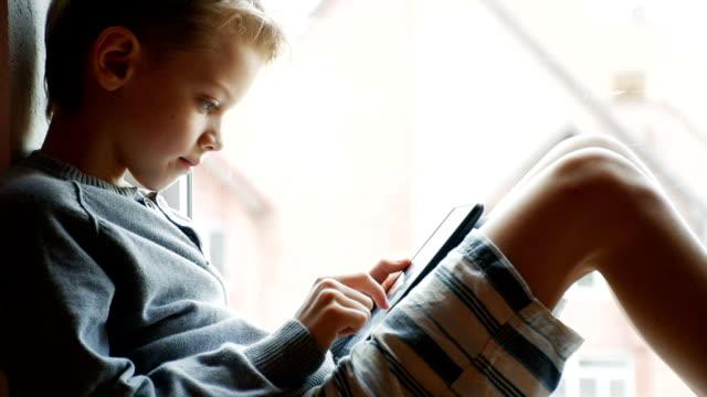boy playing on a digital tablet