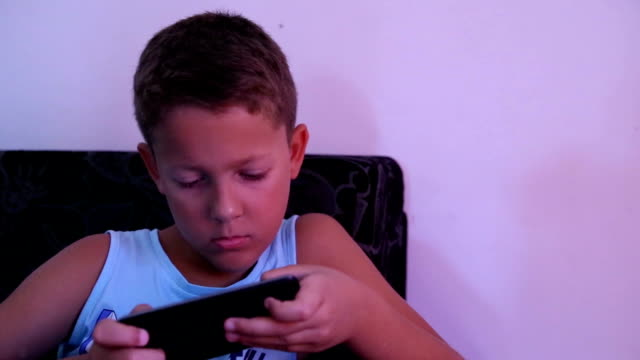 stockvideo's en b-roll-footage met een jongen spelen op mobiele telefoon pan links portret - alleen jongens