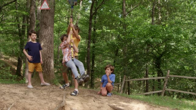 boy playing on rope and friends standing in forest - pre adolescent child stock videos & royalty-free footage