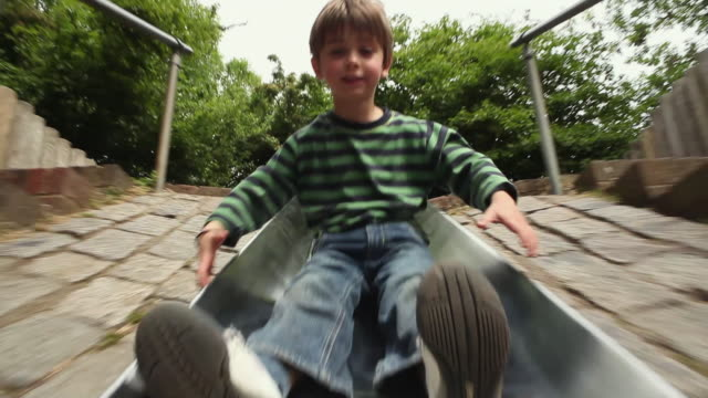 vídeos de stock, filmes e b-roll de ws pov boy (4-5) playing on slide, moving down and laughing / london, united kingdom  - deslizar