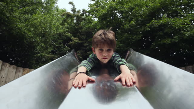 ms pov boy (4-5) playing on slide, moving down and laughing / london, united kingdom  - rutschen stock-videos und b-roll-filmmaterial