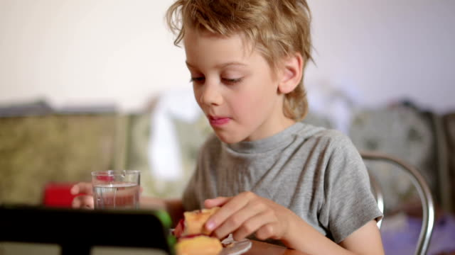 boy playing on the laptop while eating, close up - netbook stock videos and b-roll footage
