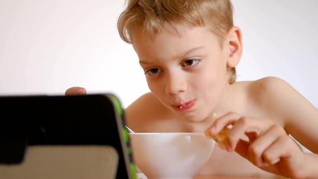 遊んでいる男の子のノートパソコンでのお食事 - unhealthy eating点の映像素材/bロール