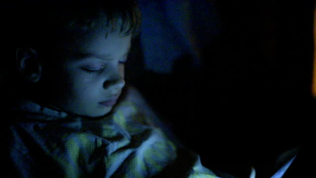 boy playing on the tablet at night