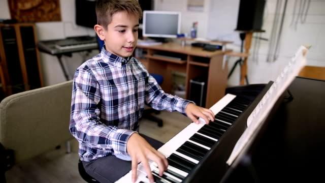 vídeos de stock, filmes e b-roll de rapaz tocando piano - dedilhando instrumento