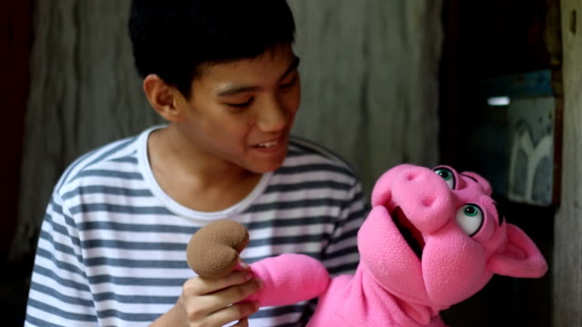 boy playing pig hand puppet