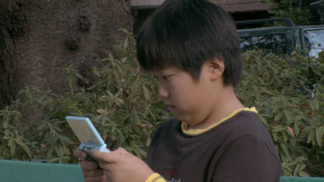 cu boy (8-9) playing portable game player sitting on bench in park / tokyo, japan   - handheld video game stock videos & royalty-free footage
