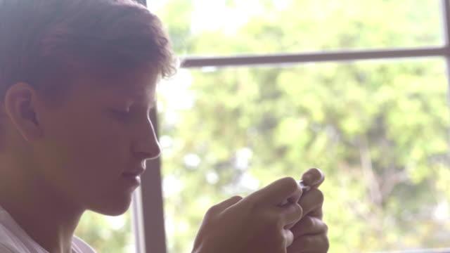 vidéos et rushes de garçon jouant le téléphone intelligent - jeunes hommes