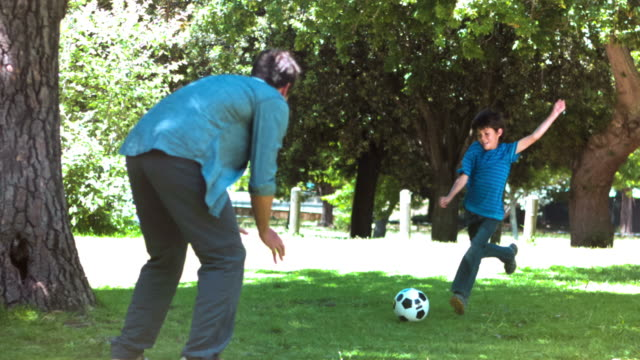 boy playing soccer in slow motion with his father - kicking stock videos & royalty-free footage