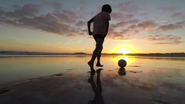 vidéos et rushes de boy playing soccer on a beach at sunset - dimanche