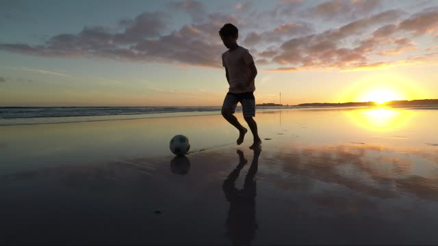 Boy playing soccer on a beach at sunset