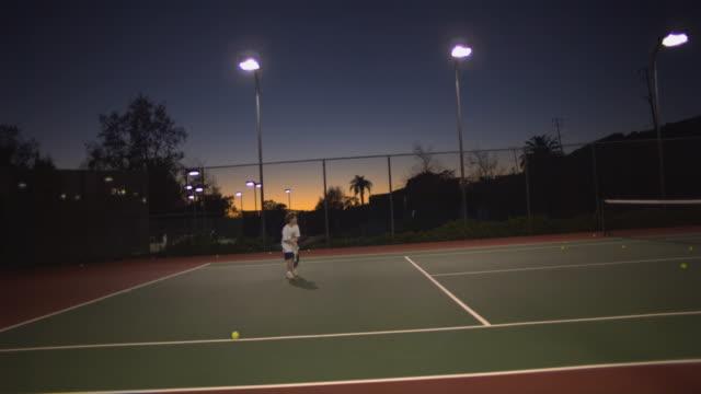 WS, Boy (6-7) playing tennis at dusk, Santa Barbara, California, USA