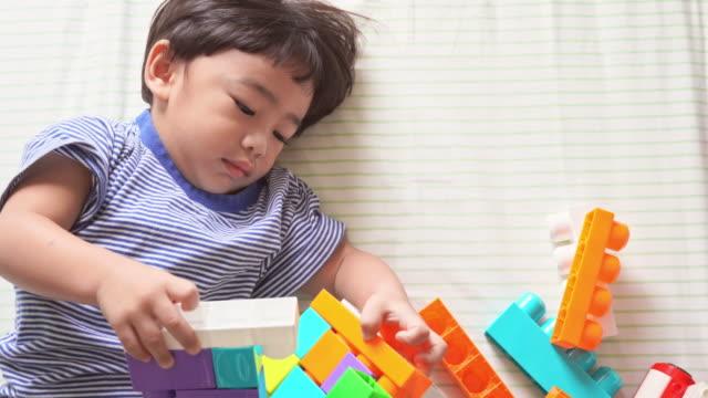 vidéos et rushes de garçon jouant le jouet sur le lit - 2 3 ans
