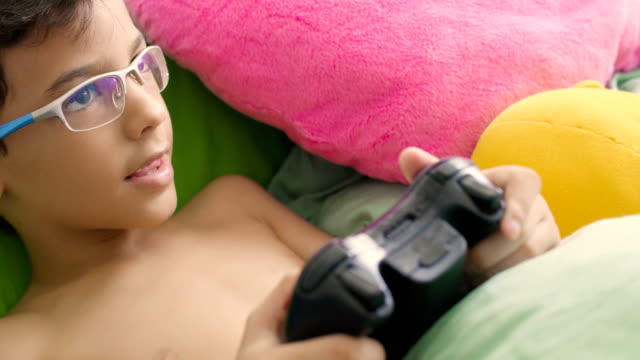 boy playing video game in bed - teenage boys stock videos & royalty-free footage
