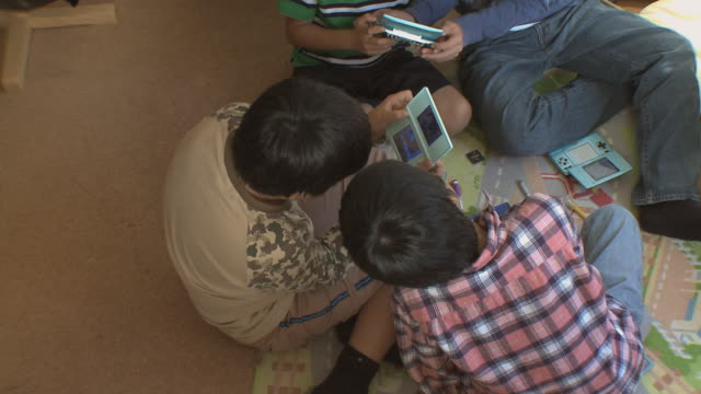 vídeos y material grabado en eventos de stock de ms boy (8-9) playing video game in kids room / tokyo, japan   - juego electrónico de bolsillo