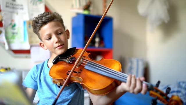 vídeos de stock, filmes e b-roll de boy playing violin at home - violino