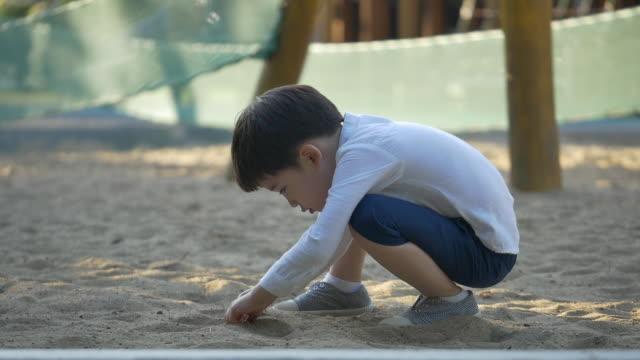 vídeos de stock e filmes b-roll de a boy playing with a dirt in the playground - cara para baixo