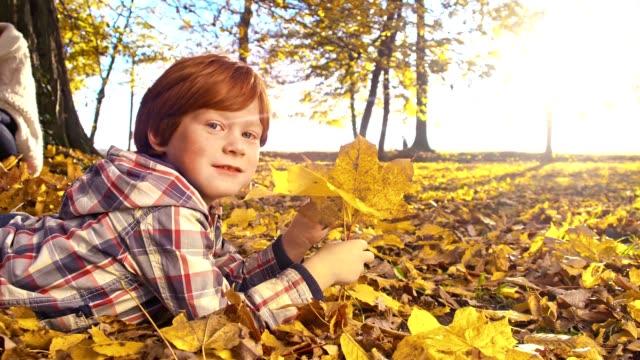 SLO MO – Jungen spielen mit Herbst Blatt