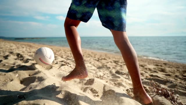 boy playing with ball on the beach - kicking stock videos & royalty-free footage