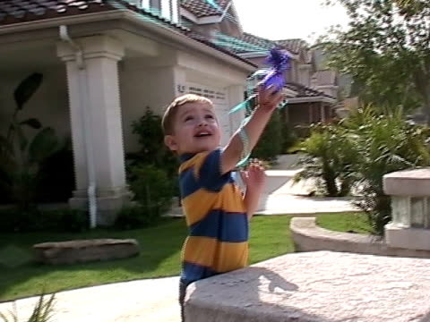 cu, boy (2-3) playing with balloons in front of house, simi valley, california, usa - maglietta polo video stock e b–roll