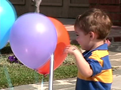 cu, zo, ms, boy (2-3) playing with balloons in front of house, simi valley, california, usa - maglietta polo video stock e b–roll
