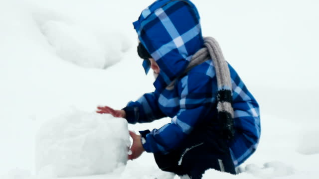 Boy playing with big snowball
