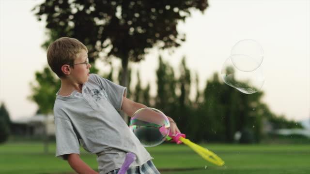 ms pan boy (12-13) playing with bubble wand in park / orem, utah, usa - orem utah stock videos & royalty-free footage