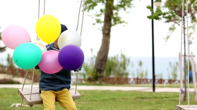 boy playing with colorful balloons in park - swing stock videos and b-roll footage