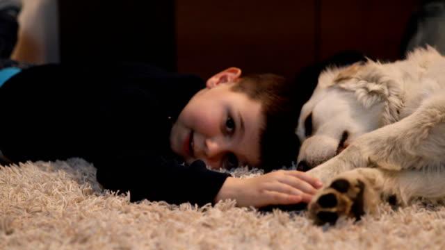 Pojke som leker med hunden hemma