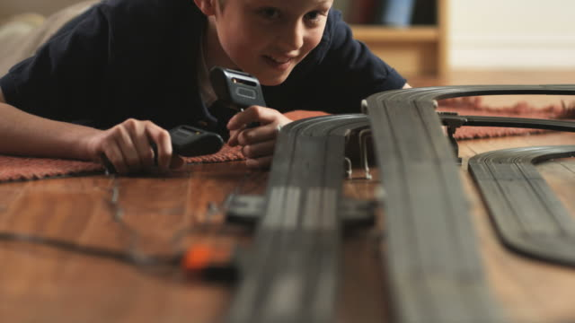 CU TU Boy (10-11) playing with electric slot cars / Orem, Utah, USA.