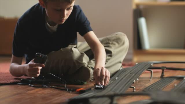 vídeos y material grabado en eventos de stock de cu tu boy (10-11) playing with electric slot cars / orem, utah, usa. - orem
