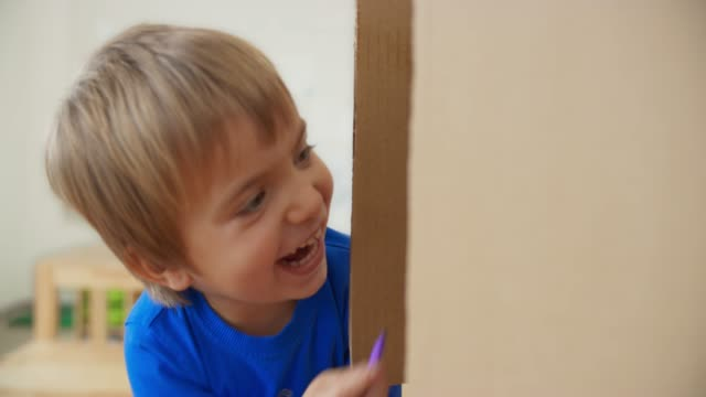 boy playing with his dad hiding in a carton box - hiding stock videos & royalty-free footage