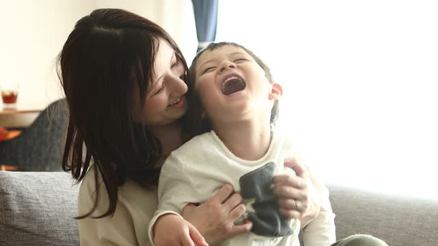 a boy playing with his mother on her lap - childhood stock-videos und b-roll-filmmaterial