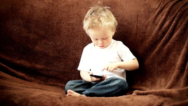 junge spielt mit mobile phone - schulkind nur jungen stock-videos und b-roll-filmmaterial