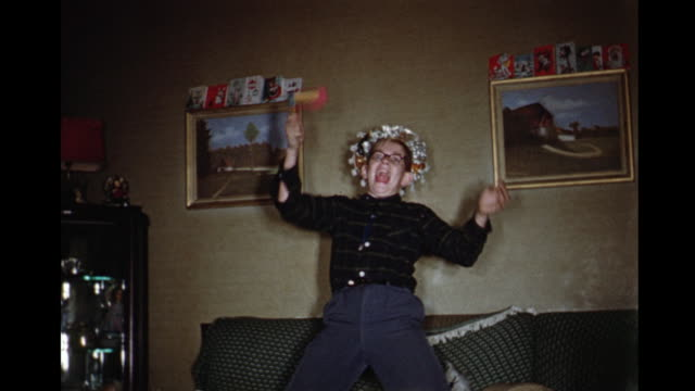 1960 MS Boy (12-13) playing with New Year's hats and noise maker, Toronto, Ontario, Canada