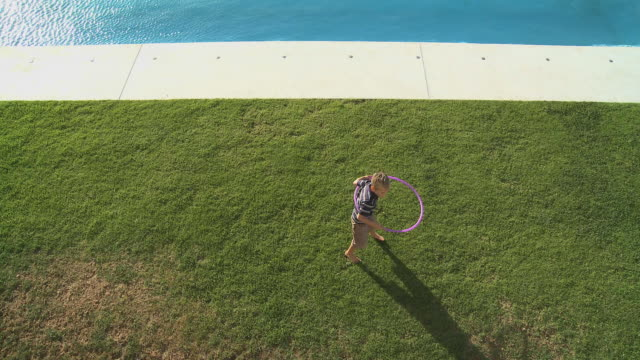 ws boy (6-7) playing with plastic hoop on poolside / cape town south africa - poolside stock videos & royalty-free footage
